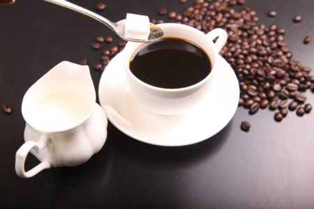 A Cube of Sugar Being Added to a Cup of Coffee