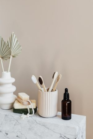 Argan Oil Next to a Tooth Brush Container and Other Things