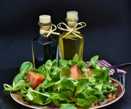 A Plate of Salad and Two Bottles of Oil