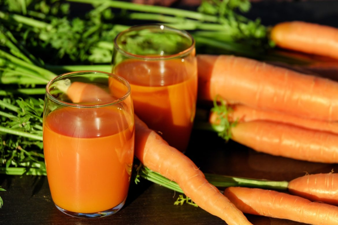 Whole Carrots and Glasses of Carrot Juices