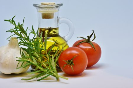 A Jar of Oil Surrounded by Tomatoes, Herbs and Onions