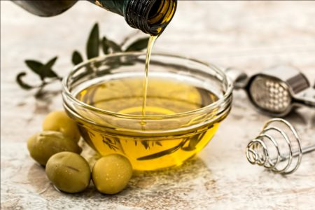 Olive Oil Being Poured in a Bowl