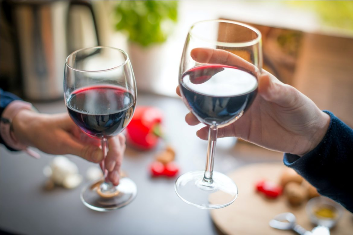 People Holding Glasses of Red Wine