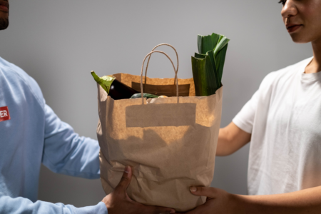 Grocery Bag Being Shared Among Two People