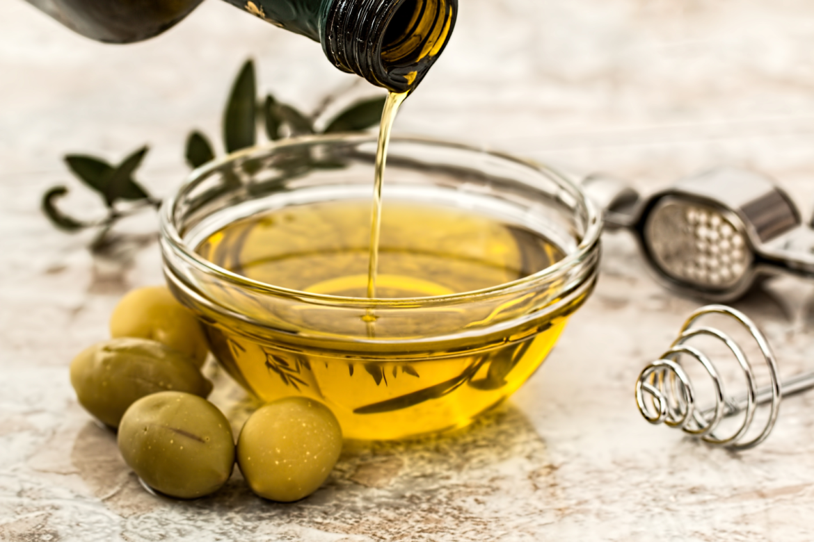 A Bowl of Oil Next to Some Olives
