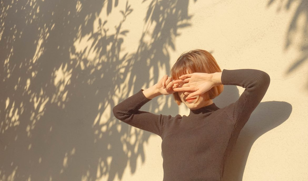 Person Blocking Sunlight with Their Hands