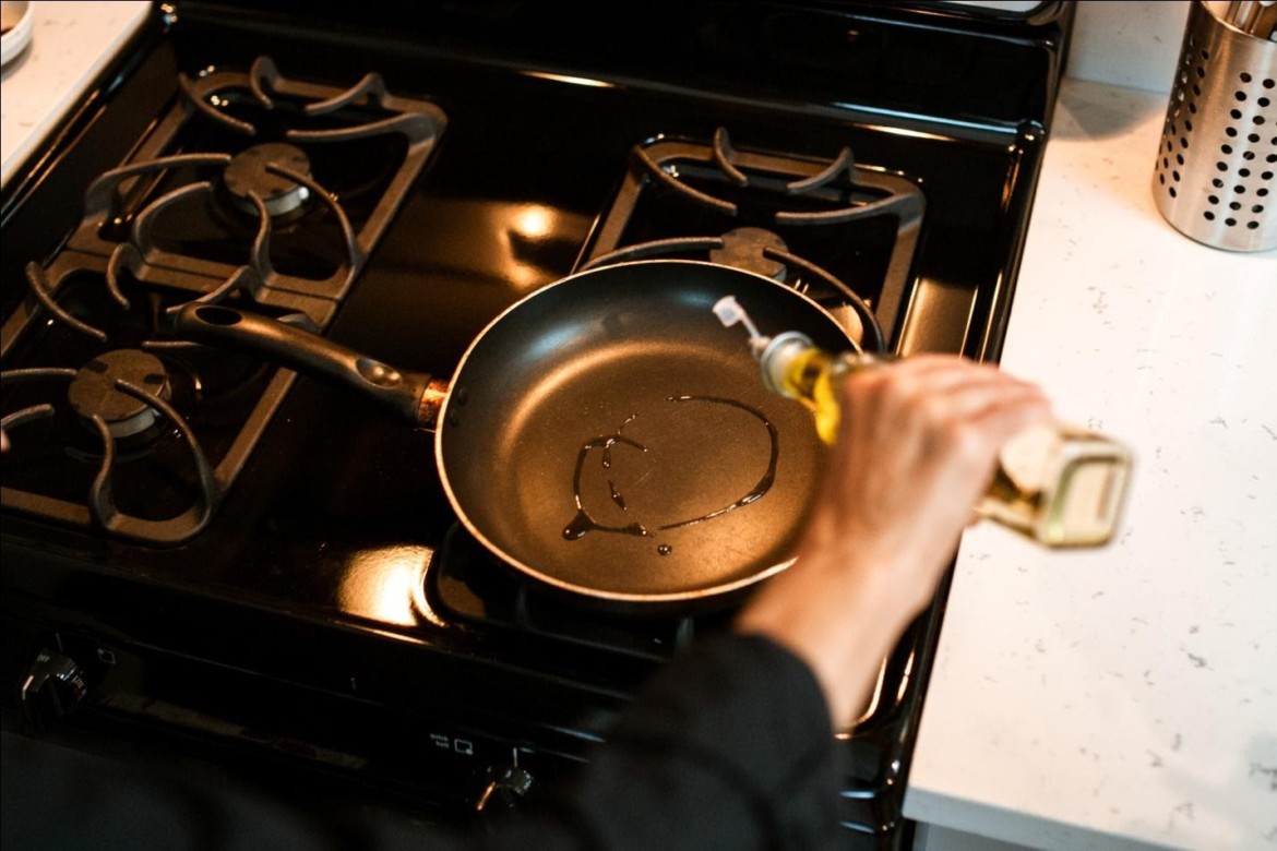 Person Pouring Oil in a Pan