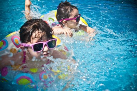 Two Kids Wearing Floats and Sunglasses while in the Pool